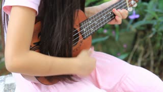 Little Asian child playing ukulele in the park
