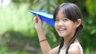 Little Asian child playing with paper airplane in the park