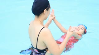 Little Asian child practices swimming with her mother