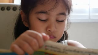 Little Asian child reading book in library