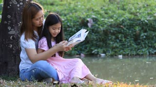 Little Asian child reading book with mother