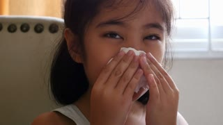 Little Asian child sick with flu sneezing and clean with tissue paper