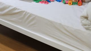 Little Asian children playing with blocks on the bed together, Tilt up shot