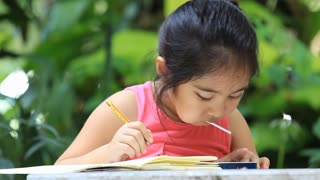 Little Asian girl drawing picture and eating candy