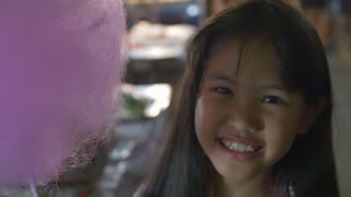 Little Asian girl eating cotton candy, slow motion