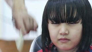 Little Asian girl getting haircut in hair salon : 4K Video