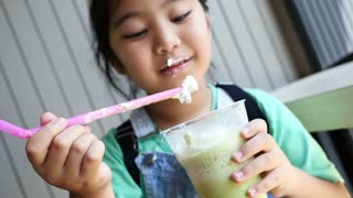 Little Asian girl has funny with cream on her lip, Slow motion shot