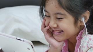 Little Asian girl in earphones using digital tablet on the bed
