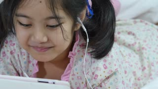 Little Asian girl in earphones using hi-tech tablet on the bed, Pan shot