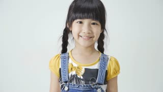 Little Asian girl is smiling on white background