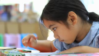 little Asian girl painting a picture on the table
