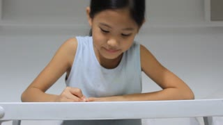 Little Asian girl painting on the bed, tilt down camera