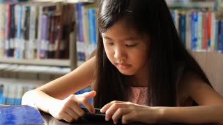 Little Asian girl play a game on smartphone in library