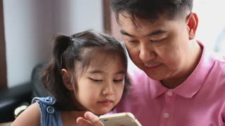 Little Asian girl playing game on mobile phone with her father