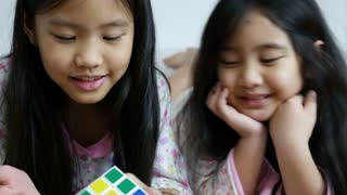 Little Asian girl playing rubik cube together on the bed