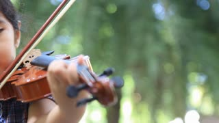 Little Asian girl playing violin in the park, Pan shot