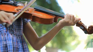 Little Asian girl playing violin in the park