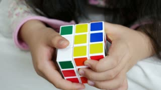 Little Asian girl playing with rubik's cube on the bed, Close up shot