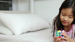 Little Asian girl playing with rubik's cube on the bed, Pan shot
