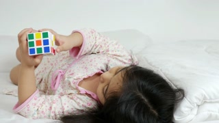 Little Asian girl playing with rubik's cube on the bed