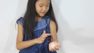 Little Asian girl puts lotion on her arm