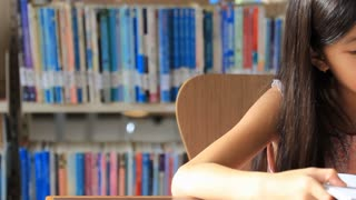 Little Asian Girl Reading A Book In Library Pan Shot Stock Video Footage Storyblocks Video