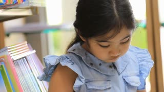 Little Asian girl reading a cartoon book in library, Tilt down shot