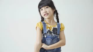 Little Asian girl singing and dancing on white background