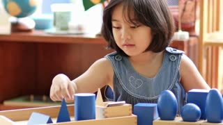 Little Asian girl stacking montessori blocks