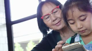Little Asian girl using smart phone with her grandmother, Happy family concept, Pan shot.