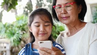 Little Asian girl using smart phone with her grandmother, Happy family concept, Slow motion shot.