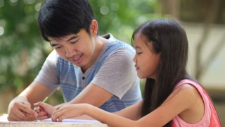 Little Asian girl with father doing homework on the table