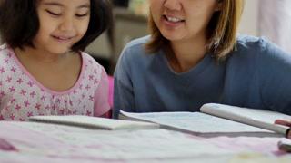 Little Asian girl with mother doing homework