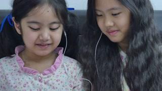 Little Asian girls in earphones using digital tablet together, Tilt up shot