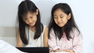 Little Asian girls laughing with tablet on the bed