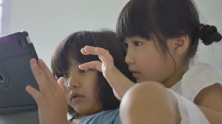 Little Asian girls play on tablet on the bed together