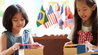 Little Asian girls stacking montessori blocks together