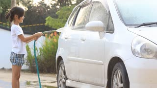 Little Asian kid washing car at home