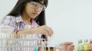 Little Asian student girl making science experiments. Education, Pan shot