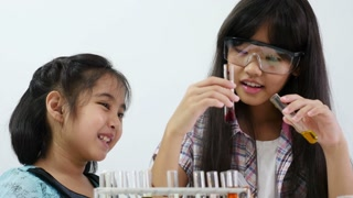 Little Asian student girl making science experiments. Education, Tilt up shot