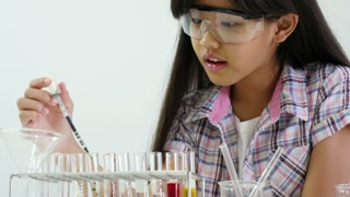 Little Asian student girl making science experiments, Tilt up shot
