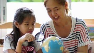 Little Asian student looking at globe while listening to teacher with magnifying glass