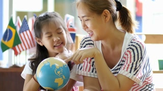 Little Asian student looking at globe while listening to teacher