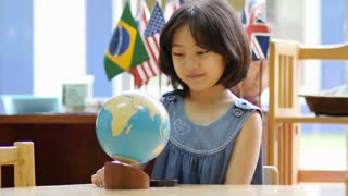 Little Asian student looking at globe with magnifying glass