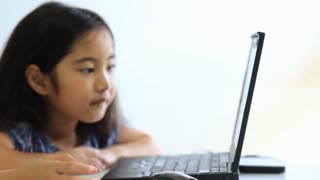 Little cute Asian girl using laptop computer and touching screen