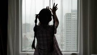 Lonely Asian girl opening the curtain and looking out the city view
