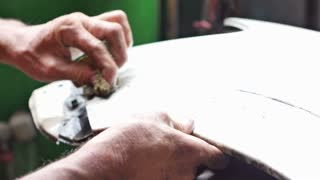 Painter scraping car bumper by hand