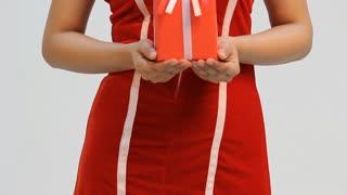 Pretty Asian woman on santa dress giving a present