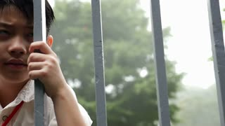 Sadness Asian boy be hide the fence, Pan shot