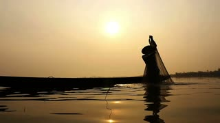 Silhouette of traditional fishermen fishing in the lake at sunrise, Slow motion
